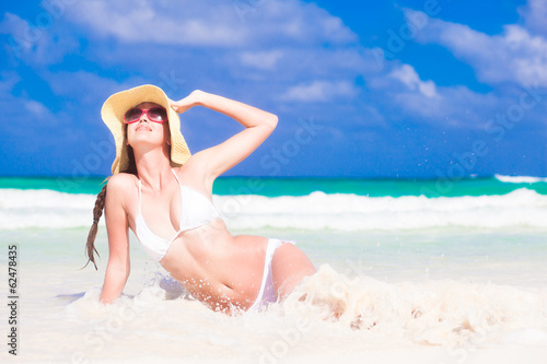 front view of beautiful young woman in sunglasses and straw hat