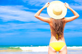 closeup back view young long haired woman in yellow bikini and