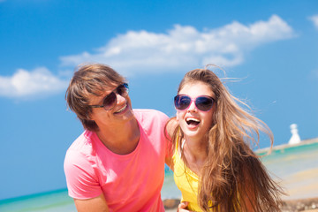Closeup of happy young caucasian couple in sunglasses smiling on
