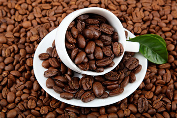 Cup with coffee beans and green leaves.