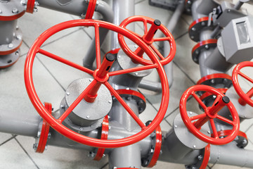 Group of red industrial valves on modern gray pipelines system