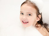 Smiling little girl washing in bath with foam