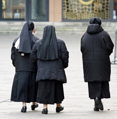 three sisters with black suit walking