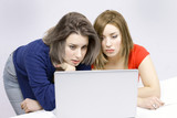 Two girls busy on laptop