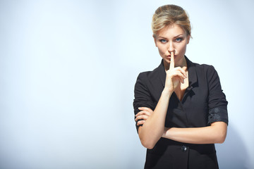 Hush. Businesswoman with finger on her lips