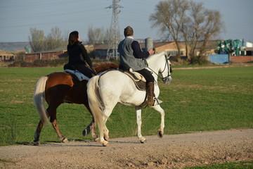 Pareja de jinetes montando en sus caballos
