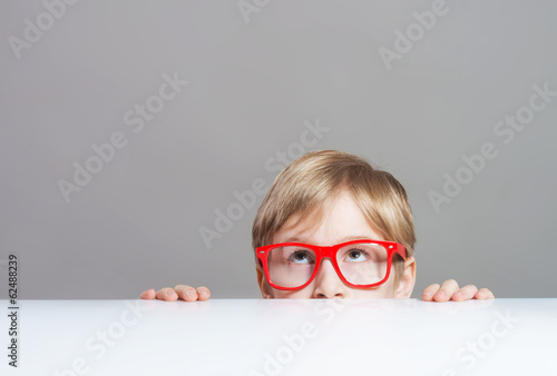 Boy in red-framed glasses looking up from behind the table