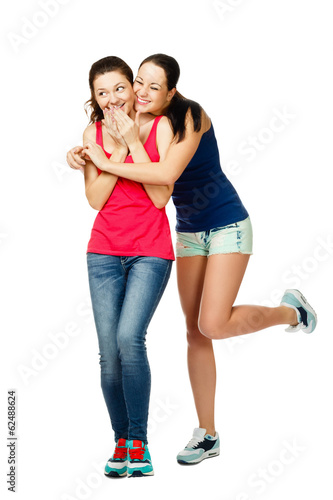 two young stand embracing and laughiing women