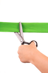 hands cutting green ribbon with scissors