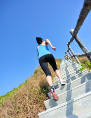 fitness woman running up at stone stairs to mountain peak