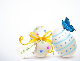 Zwei Ostereier mit Etikett und Schmetterling