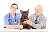 Male veterinarian, a dog and elderly gentleman posing