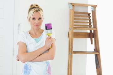 Beautiful woman holding paint brush in new house