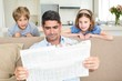 Father and children reading newspaper