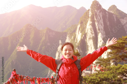 cheering woman hiker open arms at peak of mountain huashan