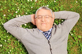 Mature man lying on green grass