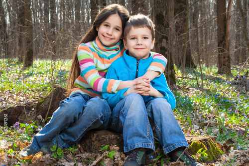 Two kids together sitting in the forest