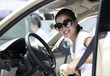 happy woman driver buckle up before driving a car