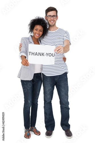 Portrait of a smiling couple holding a thank you note