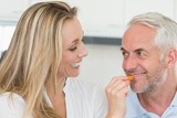 Happy woman feeding her partner vegetable piece
