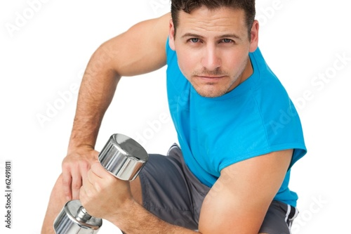 Portrait of a fit young man exercising with dumbbell