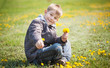 Boy plays with dandelion