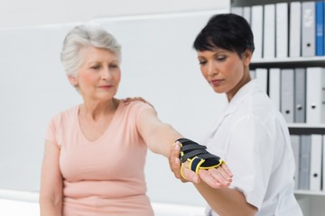 Female doctor fixing wrist brace on senior patients hand