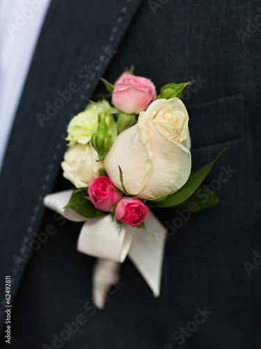 White and pink rose wedding boutonniere on suit of groom