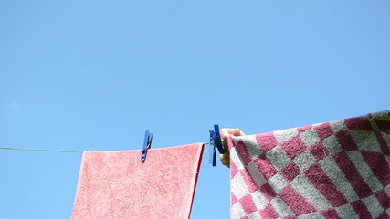 Long haired woman hang clothes to dry on rope after laundry