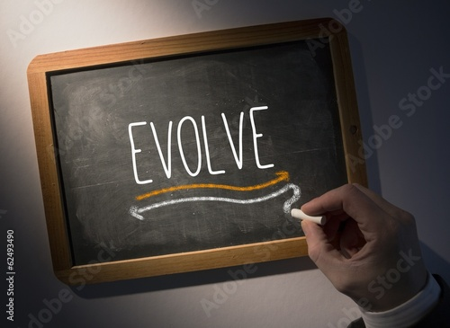 Hand writing Evolve on chalkboard