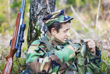 Young recruit with optical rifle in forest near tree