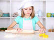 Little girl preparing cake dough in kitchen at home