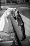 Monochrome photo of bride and groom kissing on pier at sunny day