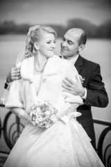Monochrome photo of mid-aged groom hugging bride from back