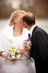 Closeup shot of aged groom and bride kissing against river