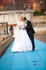 Outdoor portrait of groom kissing bride on pier near river