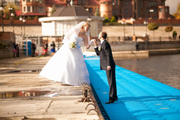 Photo of bride and groom kissing on pier at sunny day