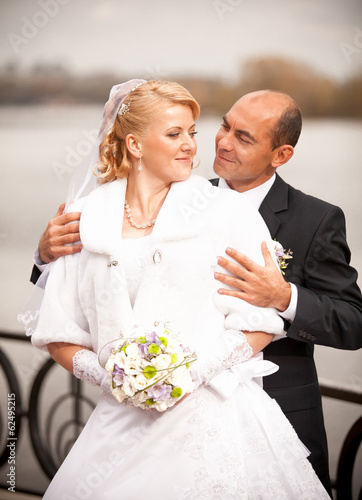 closeup portrait of mid-aged bald groom hugging bride from back