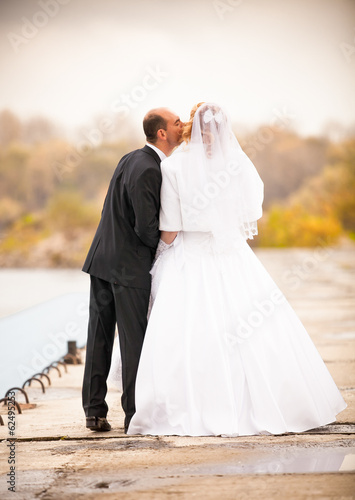 Photo from back of just married couple kissing against river