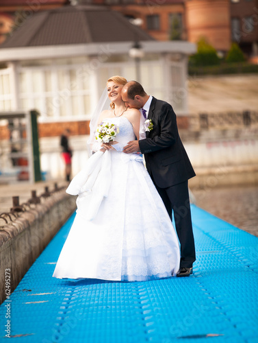 Full length portrait of handsome groom kissing bride on pier