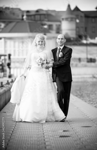 Monochrome shot of adult bride and groom walking on pier