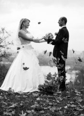 Black and white photo of bride and groom dancing at autumn park