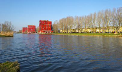 Red highrise along a canal in winter