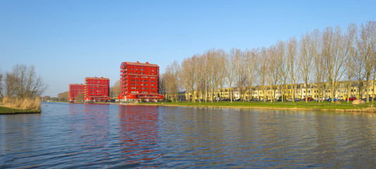 Red highrise along a canal in summer