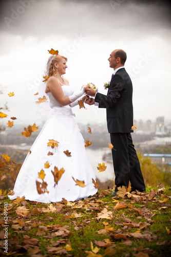 Just married couple holding hands at autumn windy day