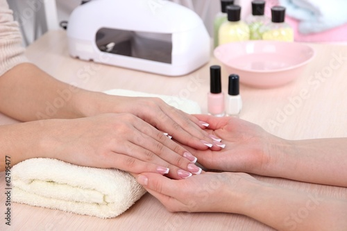 Young woman getting manicure in beauty salon