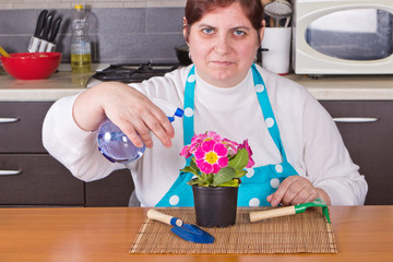 Middle-aged woman taking care of flower