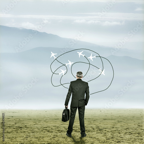 Businessman in desert with arrows and planes