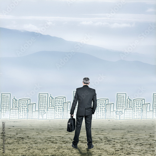 Businessman in desert with buildings on the horizon