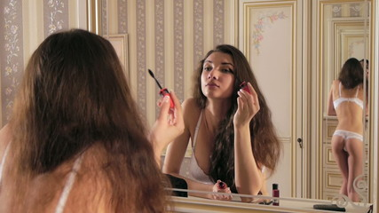 Girl paints eyelashes before a mirror